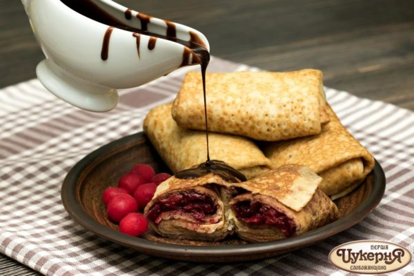блинчик с вишней и шоколадом на блюде